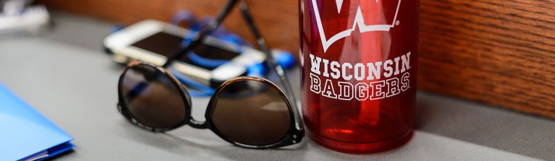 Sunglasses, iphone and UW-branded water bottle sitting on a students desk.
