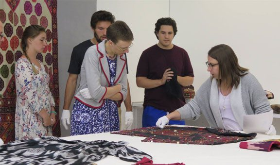 Students looking at quilts in a languages class