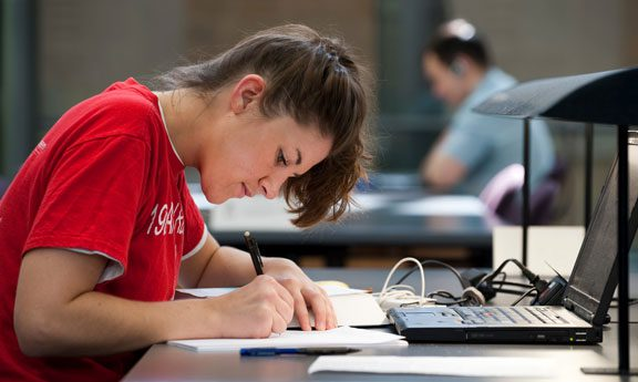 Law student in badger red working in the law library