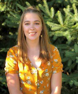headshot of student Amanda Hamm with background of spruce tree