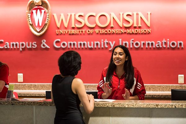 student behind a desk helping a customer at UW-Madison