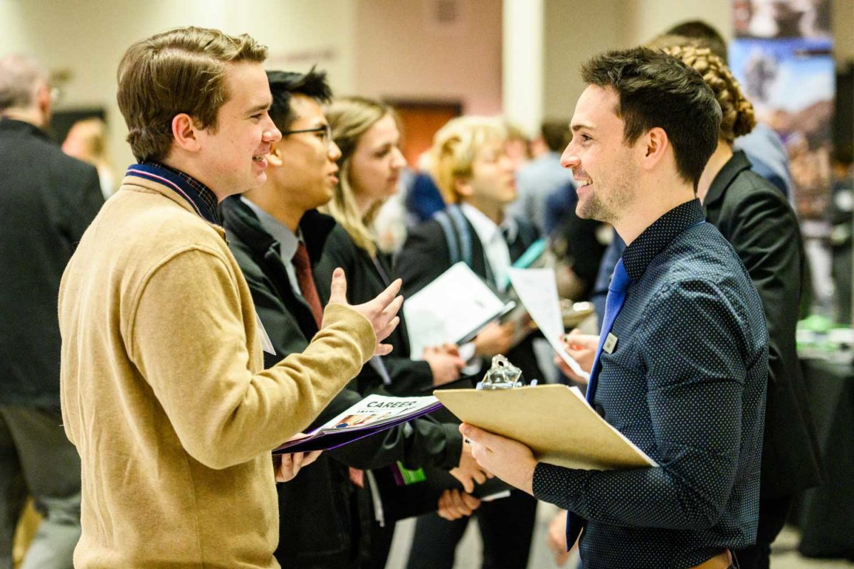 recruiter and student talking at a career fair among a crowd of other people