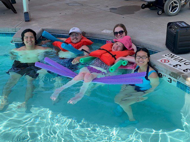 campers at Easter Seals respite camp in a swimming pool with nursing student, all smiling