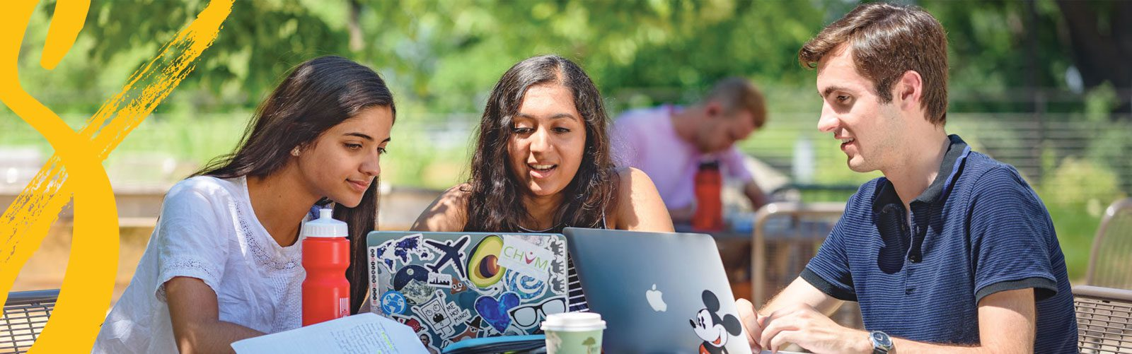 Summer student leaders working outside on laptops on a beautiful summer day.