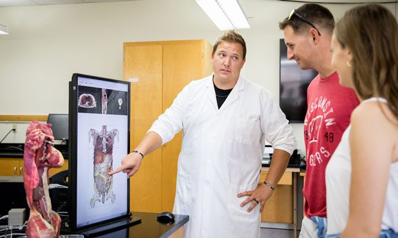 Professor instructs students in anatomy class