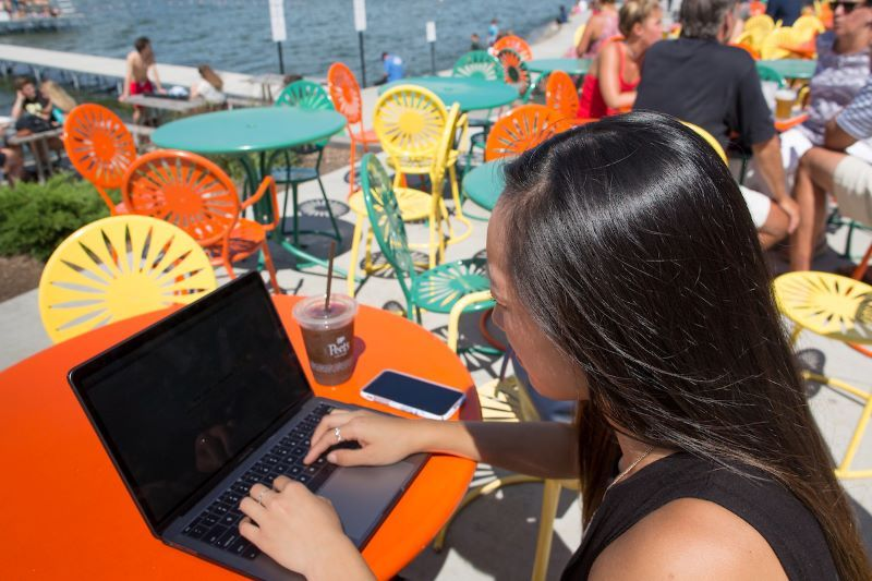 student sitting on the memorial union terrace on her computer
