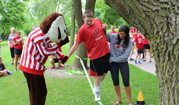 Bucky Badger and student helps blind student cross slackline