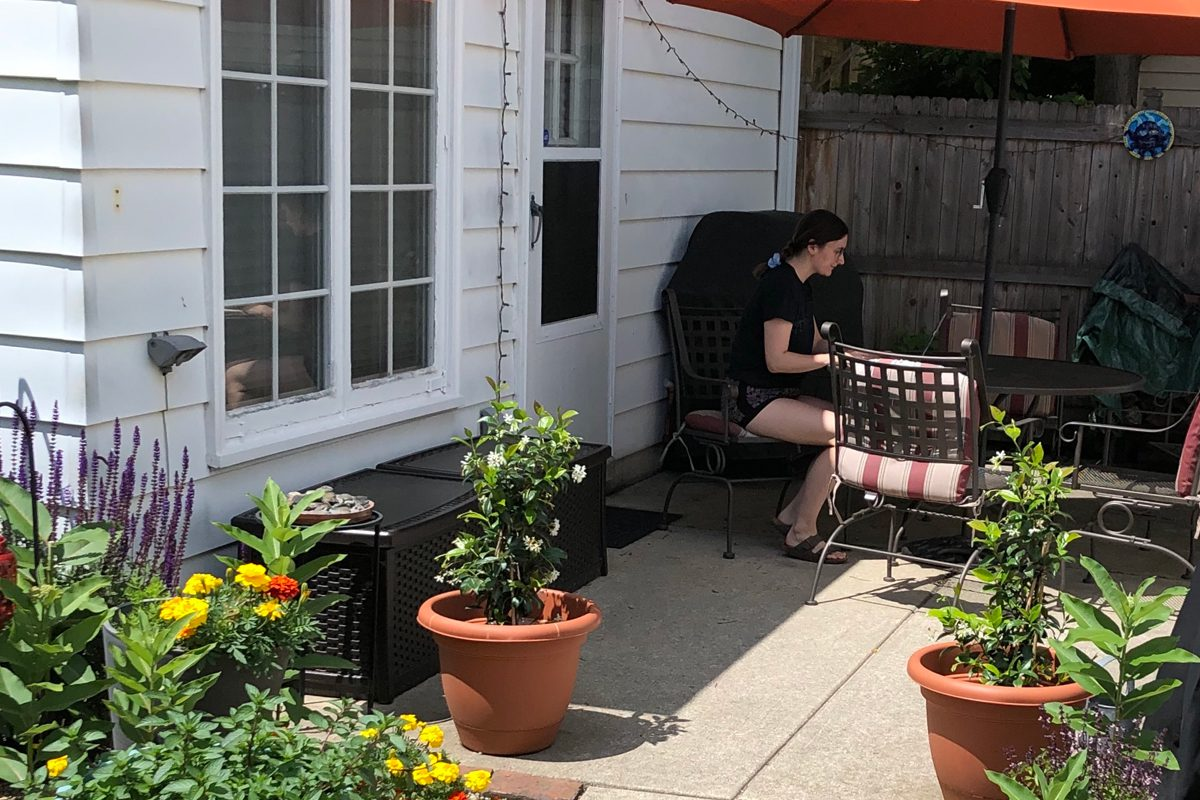 UW-Madison Summer Student Emma Bucezky studying at table with umbrella on outdoor patio, surrounded by plants