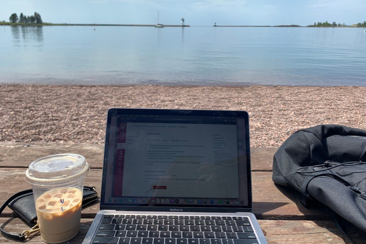 Laptop and iced coffee on rocky beach with lake view in background