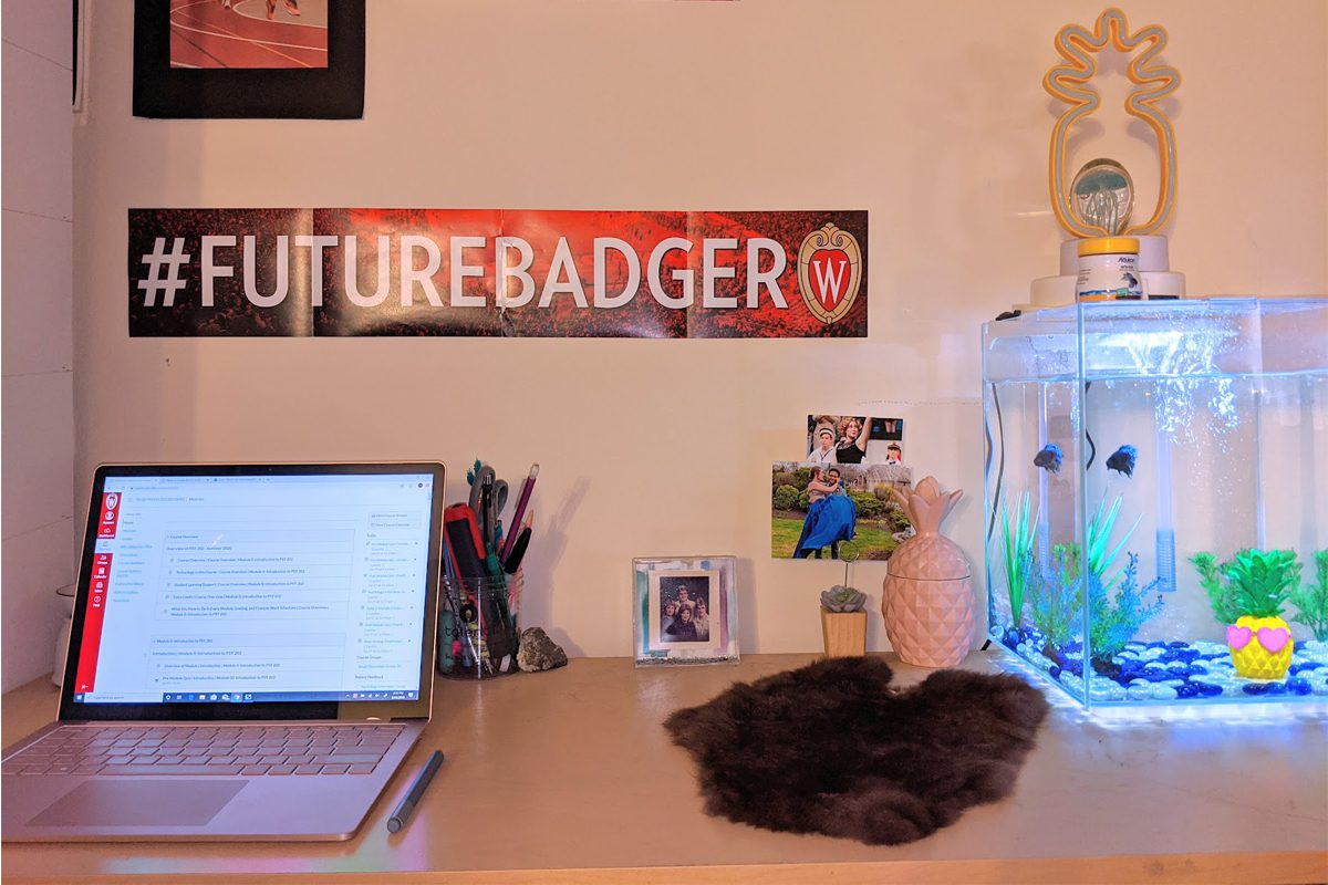 Desk with laptop and fish tank, and #FutureBadger banner on the wall