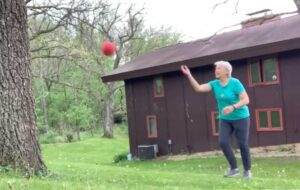 Cindy Kuhrasch tosses a red ball against a tree outside