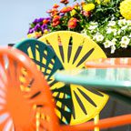 Colorful Union Terrace chairs with flowers in the background.