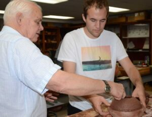 Professor Kenoyer working with a student on making pottery.