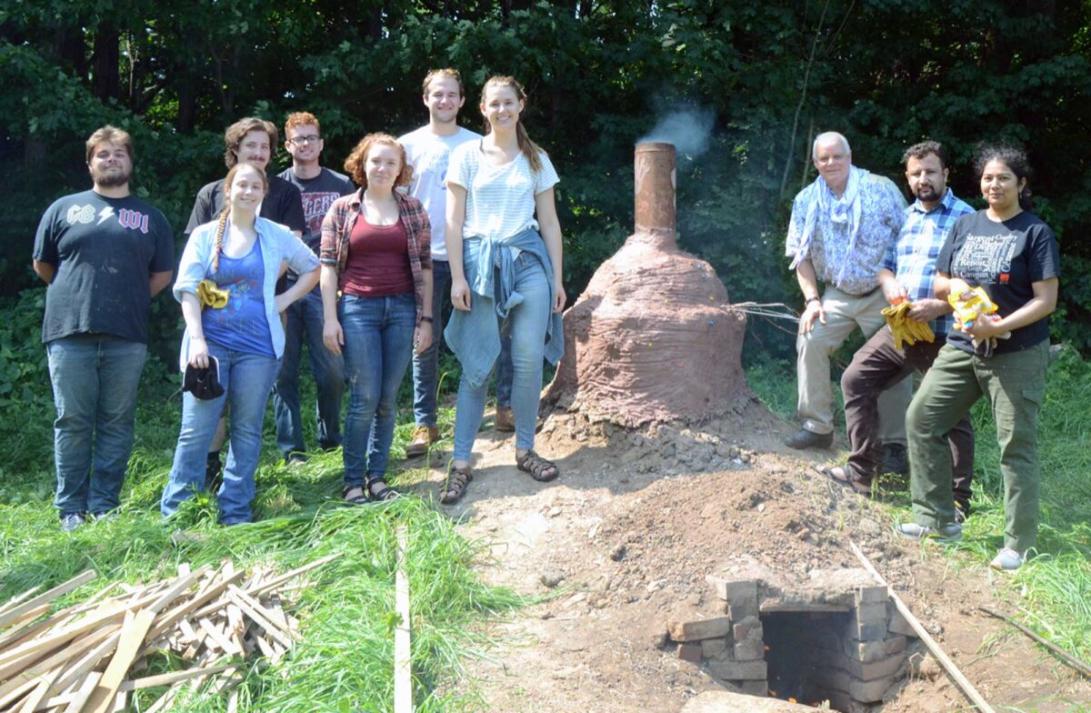 students and professor standing outside around an outdoor kiln